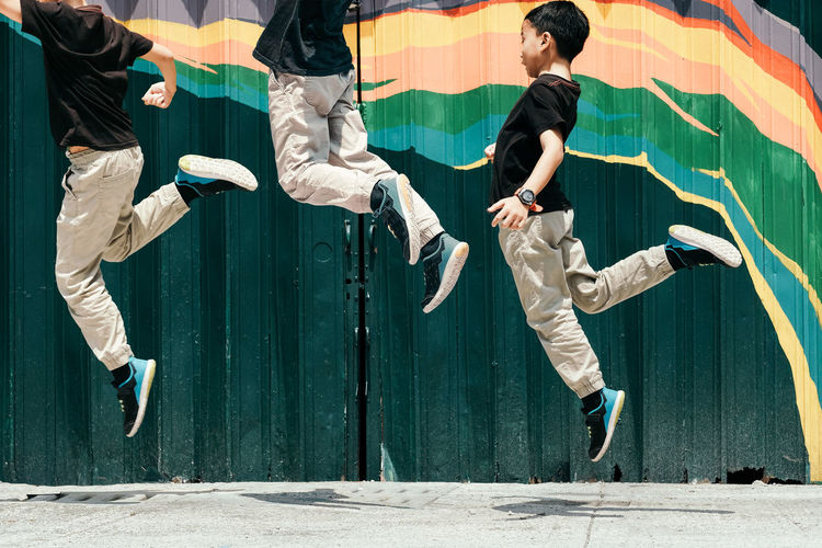 Friends jumping against wall