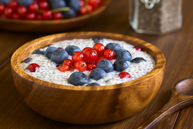 Chia (lat. Salvia hispanica) seed pudding with blueberries and redcurrants in wooden bowl, photographed on dark wood with natural light (Selective Focus, Focus one third into the pudding) Chia Meal Pudding Raw Salvia Hispanica Seed Snack Berry Berry Fruit Blueberry Breakfast Chia Pudding Currant Dairy Dairy Product Dessert Food Food And Drink Fruit Healthy Milk Raw Food Red Currant Sweet Uncooked