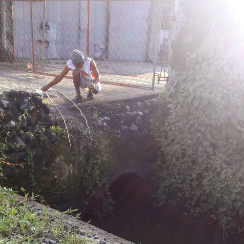 A street side fisherman Fishing Water Spraying Men Working Sunlight Sky