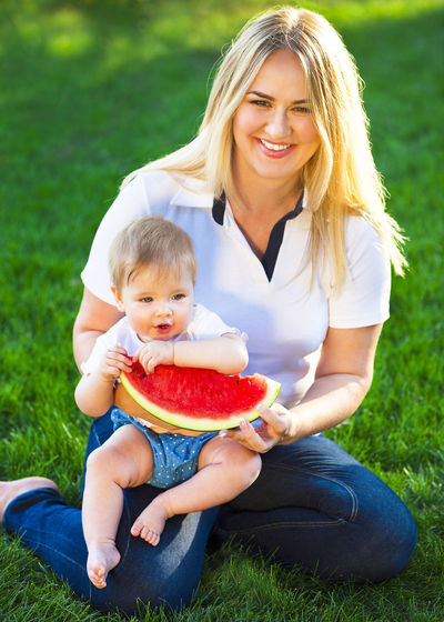 Portrait of smiling woman holding baby while sitting on grass