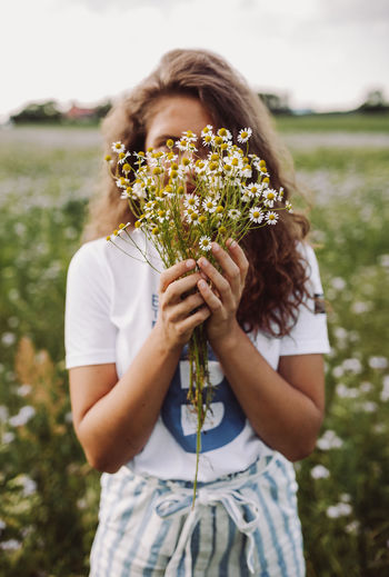 Midsection of woman holding flowering plant on field