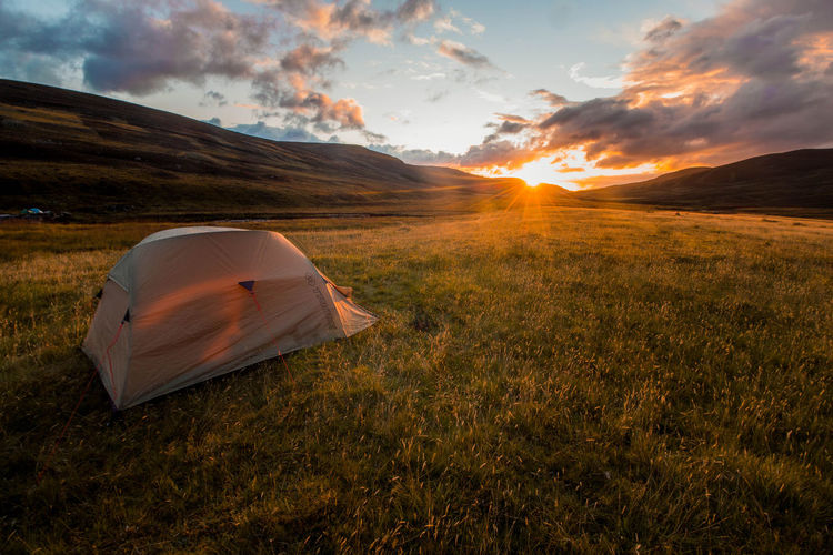 Tent on field against sky during sunset