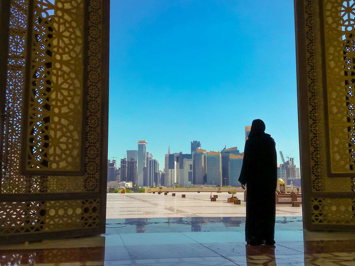 Woman with abaya dress looks at views of skyscrapers of Doha West Bay skyline outdoors State Grand Mosque in Doha, Qatar, Middle East, Arabian Peninsula. Doha Doha,Qatar Qatar City Town Waterfront Skyline Woman Model Girl Female Tourist Seascape Tourist Attraction  The Pearl, Doha The Pearl Cityscape Holiday Vacation People Mosque Architecture Mosque Door Grand Mosque Islam Islamic Architecture Islamic Muslim Muslim Woman Muslim Culture Arab Architecture Built Structure Building Exterior Sky Clear Sky Building Real People Day Rear View Blue One Person Nature Standing Lifestyles Office Building Exterior Outdoors Tower Skyscraper