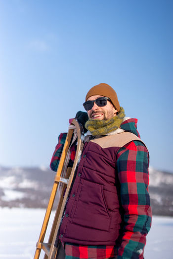 Man wearing sunglasses standing on snow against sky