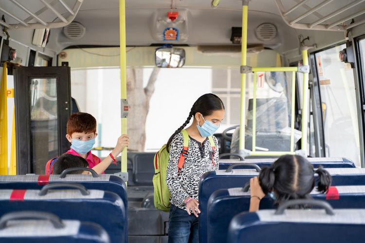 Cute girl wearing flu mask standing in bus