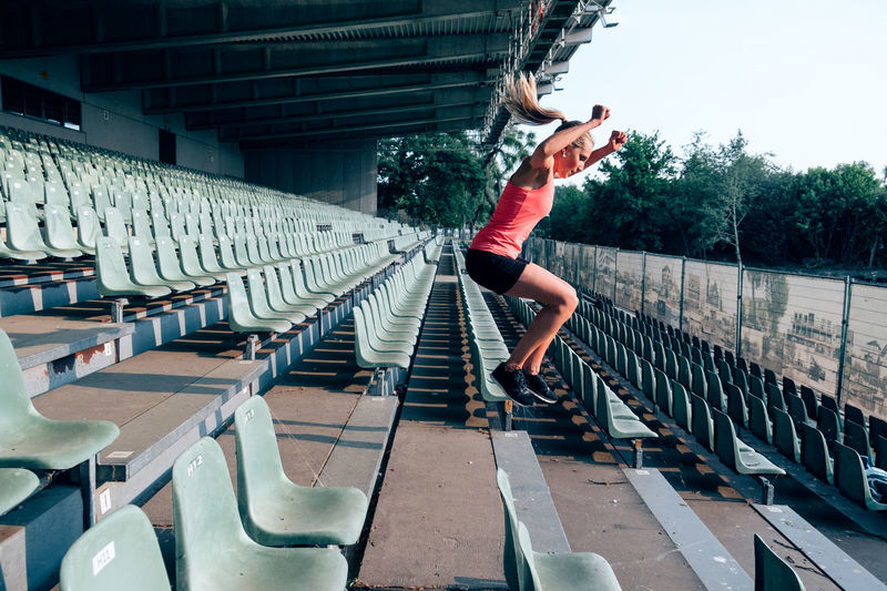 Side view of fit and healthy woman workingout at the stadium jumping up and down the steps
