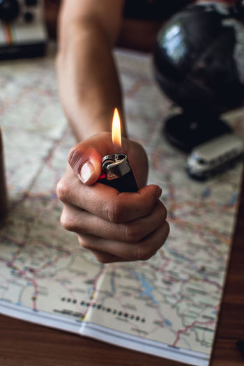 Cropped Hand Holding Cigarette Lighter Over Map