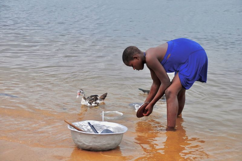 Side view of young woman washing utensil in sea