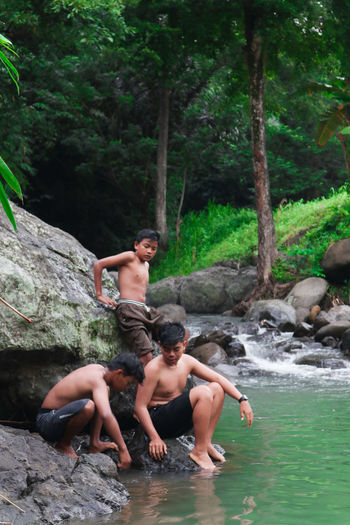 Full length of shirtless man on rocks in forest