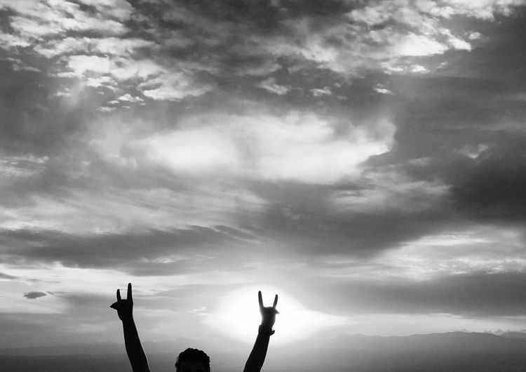Cropped image of man showing rock sign against cloudy sky
