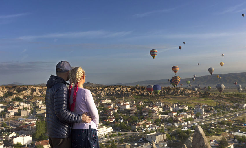 Young people watch dozens of balloons flying over the valleys of Cappadocia at dawn in central Turkey. Two People Togetherness Sky Leisure Activity Real People Women Nature Couple - Relationship Architecture Men Lifestyles Building Exterior Standing Positive Emotion People City Built Structure Adult Three Quarter Length Bonding Cityscape Outdoors