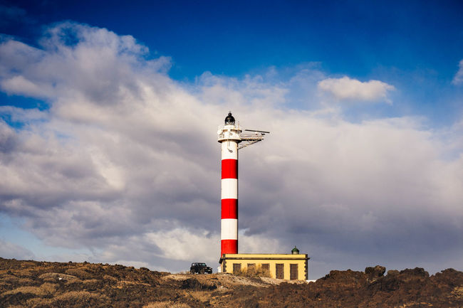 Black off road car parked near a lighthouse Freedom Travel Vacations Architecture Beauty In Nature Black Car Built Structure Cloud - Sky Day Direction Dirt Road Guidance Horizon Journey Lighthouse Nature No People Ocean Off Road Outdoors Protection Red Safety Sea Sky