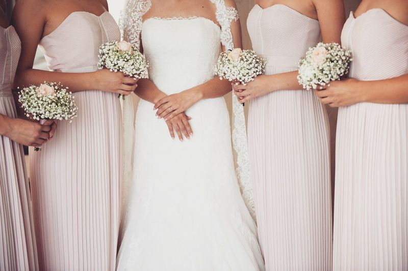 Midsection of bride with bridesmaid