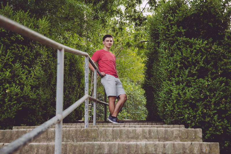 Attractive Casual Clothing Comfortable Confident  Dark Hair Day Full Body Full Length Green Color Leaning Lifestyles Lush Foliage Male Man Nature One Person Outdoors Person Plant Portrait Red Shirt Relaxed Stairway Tree Young Adult