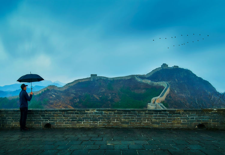 Man with umbrella standing at great wall of china against cloudy sky