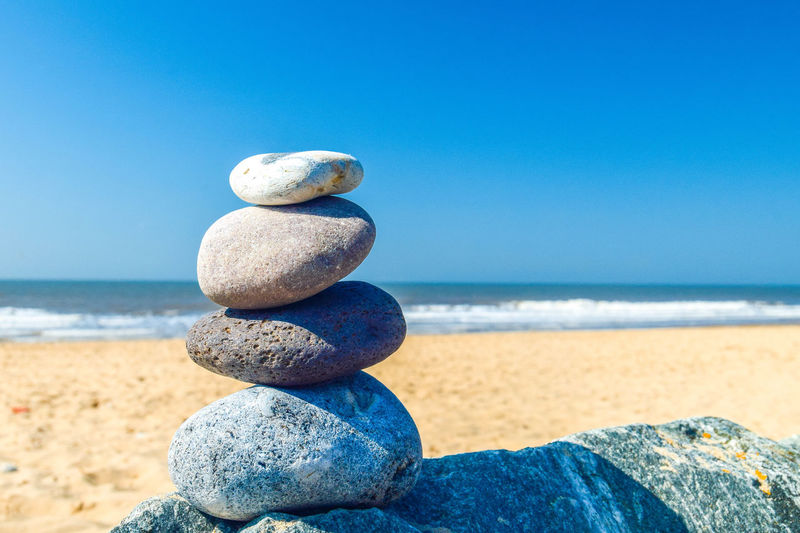 Pebble Stack Pebble Stacking Solid Stone - Object Rock Stone Land Beach No People Rock - Object Pebble Zen-like Nature Balance Stack Outdoors Sea Sky Water Horizon Blue Horizon Over Water Tranquility Clear Sky Beauty In Nature Stack Rock Space For Text Space For Copy Beach Photography