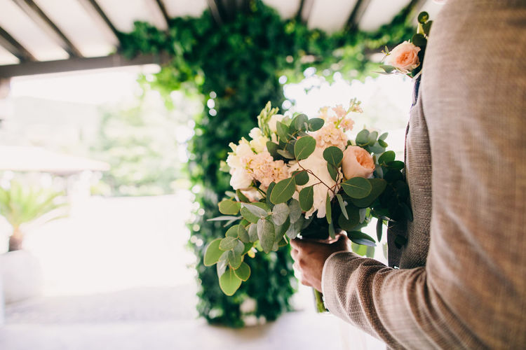Midsection Of Bridegroom Holding Flower Bouquet At Home