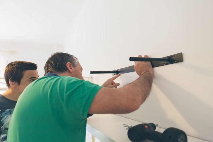 Father With Son Fixing Rack On White Wall
