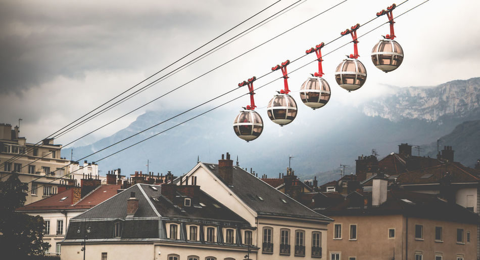 Low angle view of overhead cable cars over buildings in town