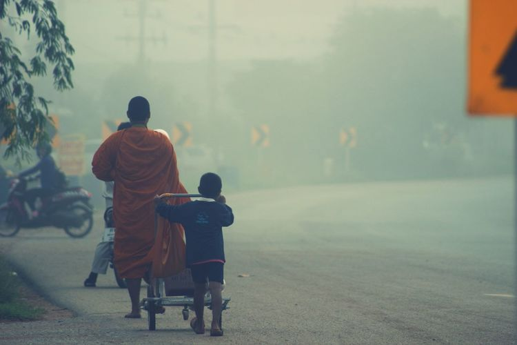 Rear View Of Monk And Boy Walking On Road During Foggy Weather