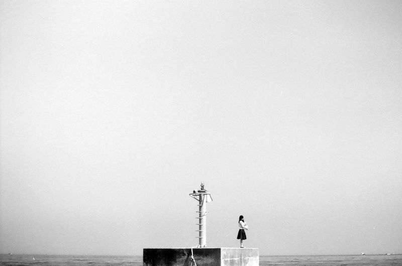 Woman Standing On Pier Against Sky