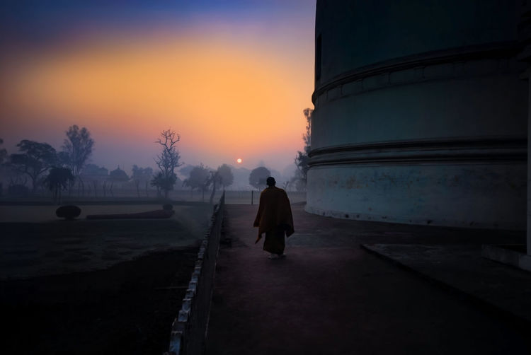Rear View Of Monk By Temple During Sunset
