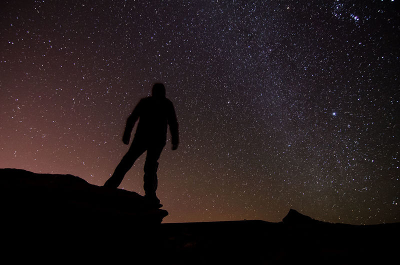Silhouette man standing on cliff against sky at night