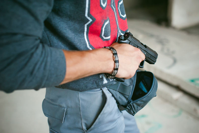 Midsection Of Man Holding Rifle