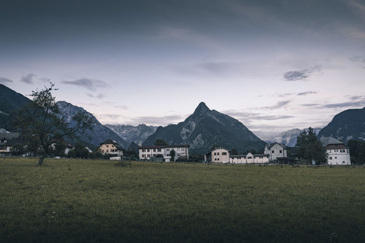 Houses on field by mountains against sky