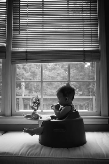 Silhouette of baby playing in chair Authentic Moments Baby Chair Lifestyle Silhouette Authentic Childhood Cute Day Family Full Length Girls Home Interior Indoors  Leisure Activity Lifestyles People Playing Real Life Real People Reality Sitting Toddler  Toy Window
