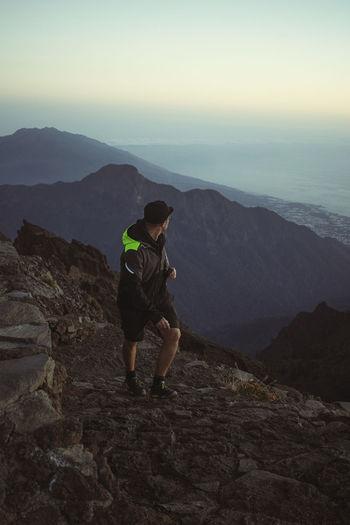 Full length of man climbing on mountain against sky