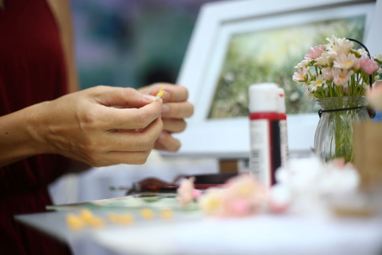 Midsection Of Woman Making Artificial Flowers