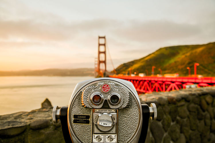 Close-up of coin-operated binoculars by sea against sky during sunrise