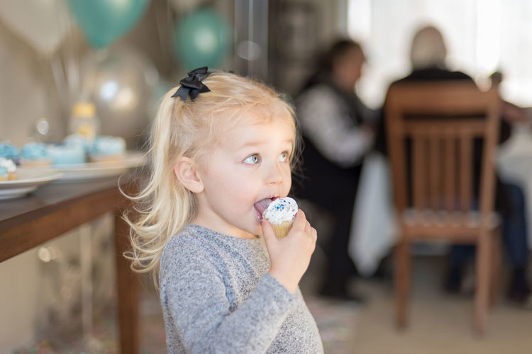 Cute girl eating cupcake at home during birthday party