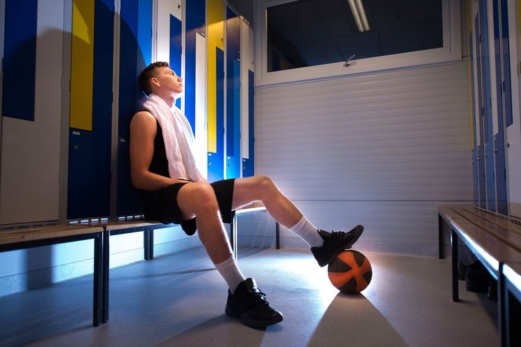 Basketball player sitting in the locker room. Boy Locker Room Basketball Sport Healthy Lifestyle Healthy Sports Champions Training Athlete Muscles Fitness One Person Full Length Sitting Side View Lifestyles Young Adult Indoors  Sport Leisure Activity Young Men Adult Exercising Relaxation Men Healthy Lifestyle Resting Dressing Room Clothing Shorts