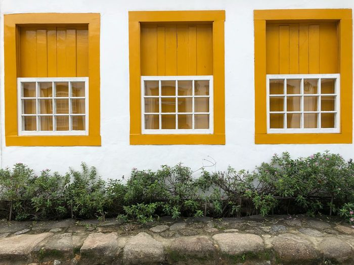 Symmetrically planned Paraty - RJ Symetrical Windows Architecture Window Building Exterior Architecture Built Structure Building Residential District House No People Day Outdoors Glass - Material Wall - Building Feature Yellow Façade Sunlight City
