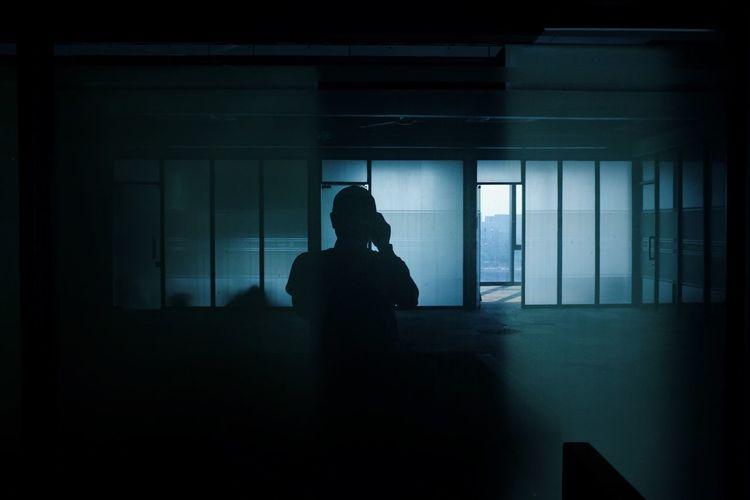 Silhouette woman sitting by window in dark room