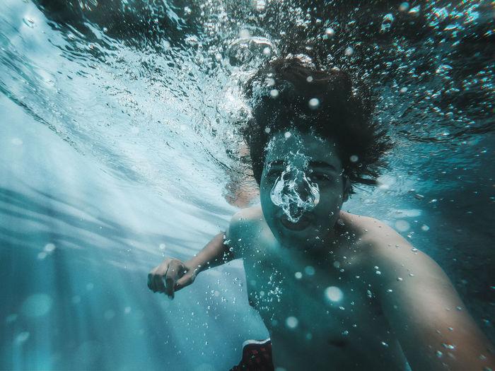 Man swimming underwater in sea