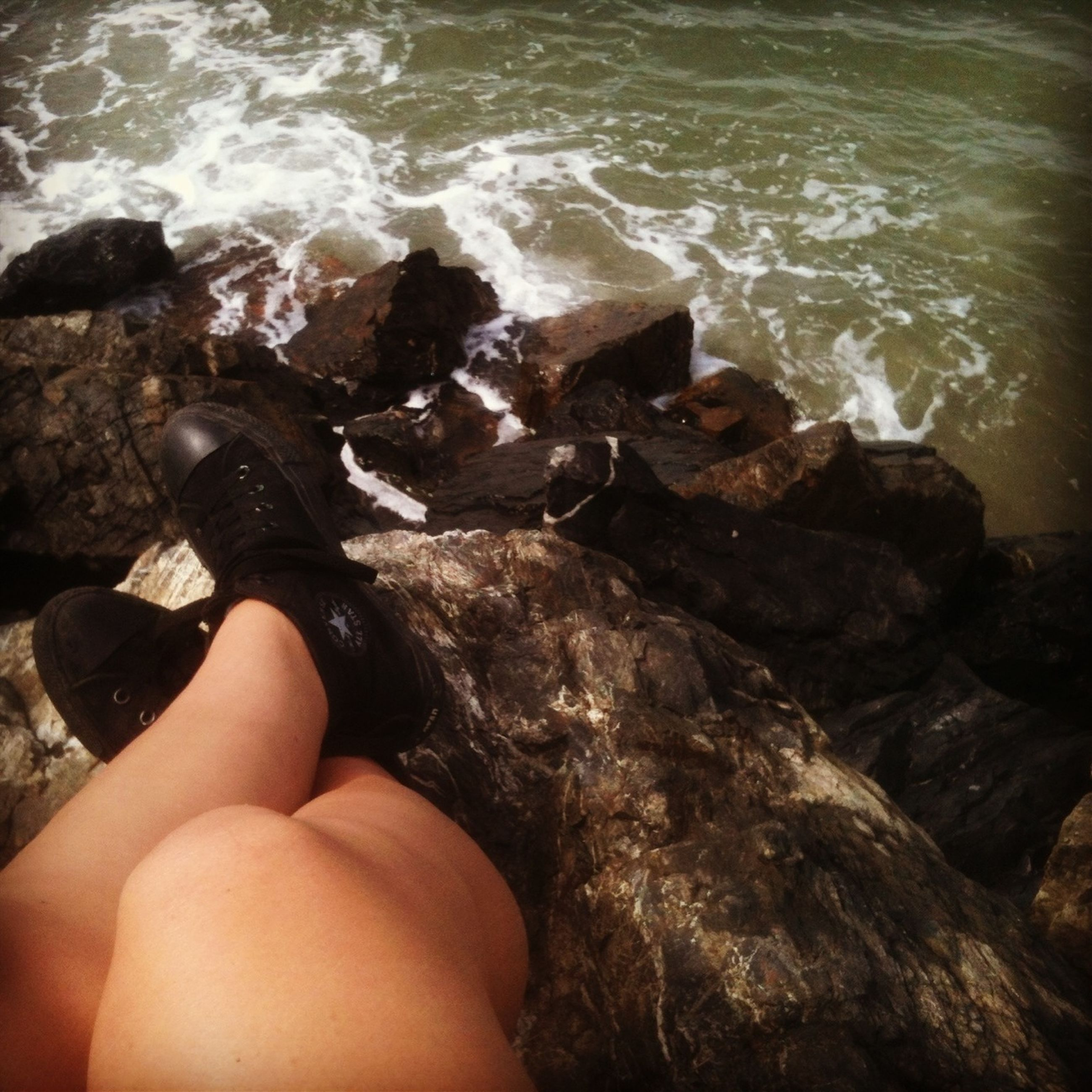 water, sea, lifestyles, beach, personal perspective, leisure activity, rock - object, person, low section, shore, high angle view, barefoot, vacations, relaxation, human foot, nature