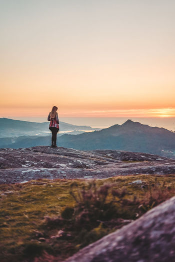 Woman standing on cliff during sunset