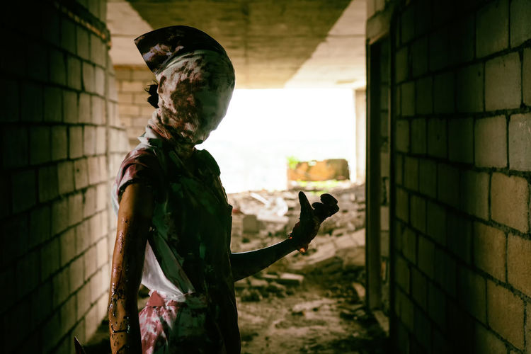 Spooky woman in mask standing at abandoned building corridor