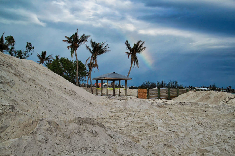 Rainbow appears in a stormy sky over the Atlantic Ocean and Sombrero Beach, which are recovering from Hurricane Irma, in Marathon Key, Florida. Hurricane Irma 2017 Rainbow Sky Sombrero Beach Florida Architecture Beach Beauty In Nature Cloud - Sky Day Hurricane - Storm Hurricane Damage Landscape Nature No People Outdoors Palm Tree Rainbow Recovery Sand Sand & Sea Scenics Sea Sky Tranquil Scene Tranquility Tree