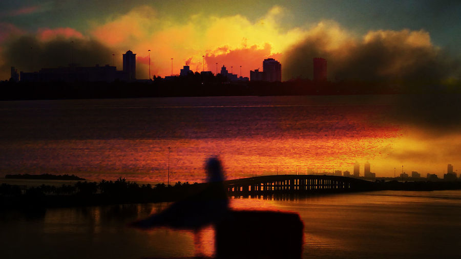 Silhouette of city at waterfront during sunset
