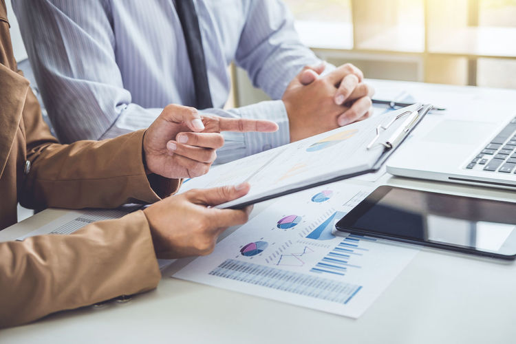 Midsection Of Businessman And Colleague Working On Graph At Office