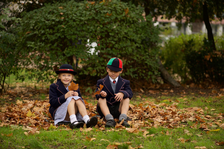 Full length of boy and girl reading books while sitting on grass