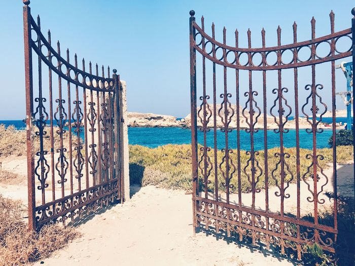 Railing Beach Gate Outdoors Sand Sea Day No People Clear Sky Water Sky Built Structure Blue Horizon Over Water Nature Architecture Rusty Metal Building Exterior Rusty Metal Structures & Lines Gate Material Rustic Style Full Frame