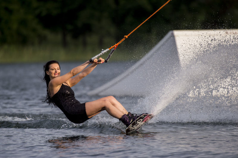Side view of woman wakeboarding in sea