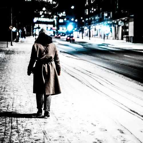 Rear view of woman walking on snow covered road