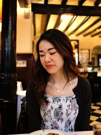Portrait of beautiful young woman in restaurant