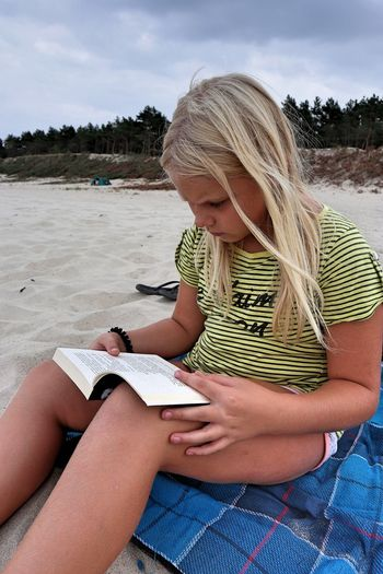 Girl with blond hair reading book sitting at beach